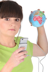Teenager with mobile and globe