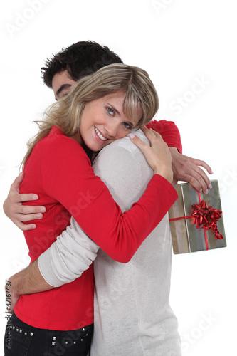 Woman holding gift hugging boyfriend