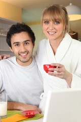 Couple having breakfast in front of their laptop