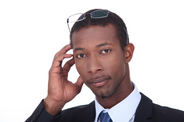 Black businessman with glasses on his head