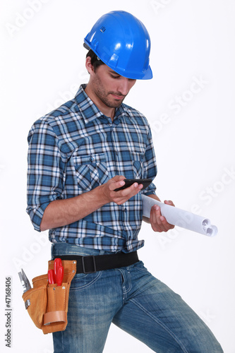 Construction worker checking his phone