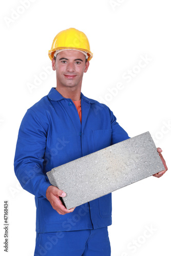 Tradesman carrying a cinder block