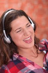 Brunette wearing headphones and singing