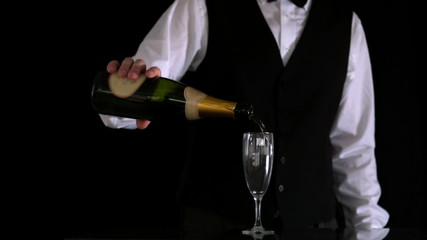 Waiter topping up champagne flute