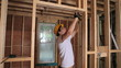 Builder hammering door frame