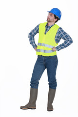 craftsman wearing hard hat standing with arms akimbo