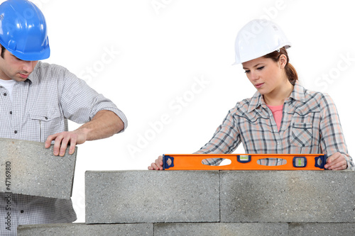 Man and woman masons stacking bricks