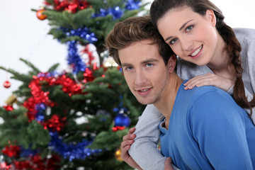 Couple gathered by Christmas tree