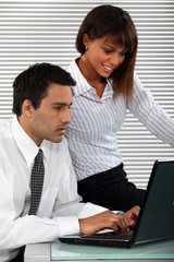 Man and woman sitting with computer