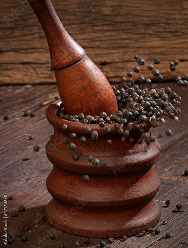 Grinding black pepper with a mortar and pestle