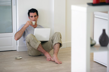 Man sat on the floor at home drinking coffee