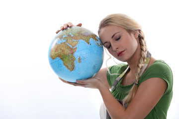 Woman in green resting her head against a large globe