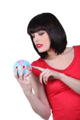 Brunette holding miniature globe