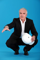 Grey haired architect crouching and offering to shake hand