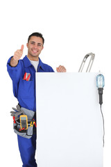 artisan near a white panel doing thumbs up