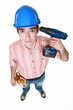 Man holding power drill against head