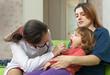 mature children's doctor examining 2 years baby