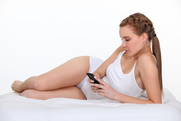 Woman lying on bed with phone