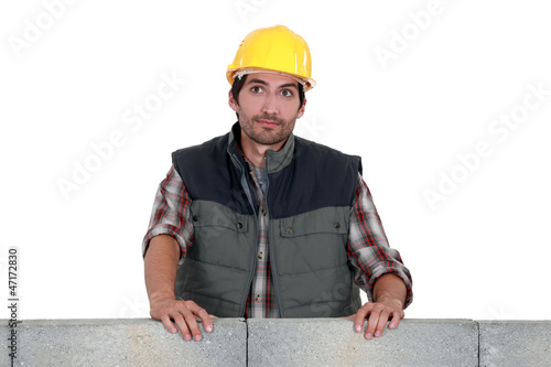 craftsman leaning on a stone block wall