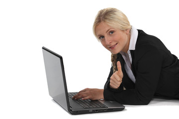 A businesswoman lying on the floor with her laptop.
