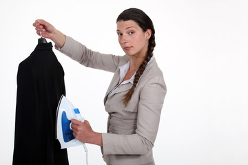 A businesswoman ironing her jacket.