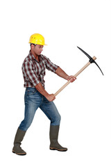 Building worker using a pickaxe, studio shot