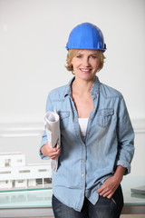 Woman in hard hat with architect's plans and model