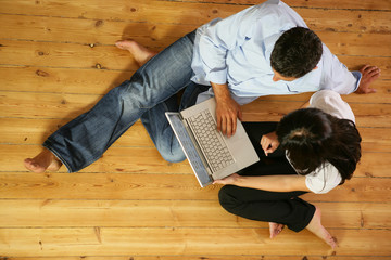 Couple in living-room with laptop computer, top-view