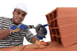 bricklayer at work with red bricks indoors