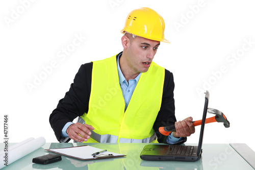 Clumsy architect smashing laptop with hammer