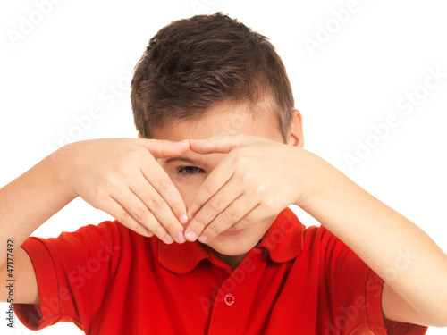 Young boy looking through heart shape