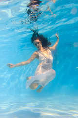 Woman in a white dress underwater in swimming pool