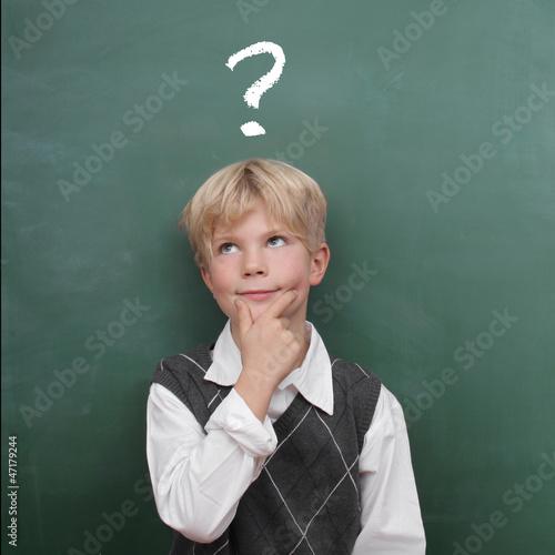 Kind fragend vor der Tafel