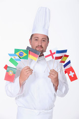 A chef holding a bunch of flags.