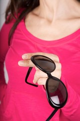black sunglasses on pink sweater background