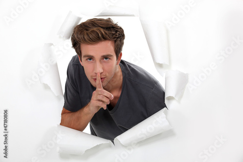 young man holds finger before his mouth