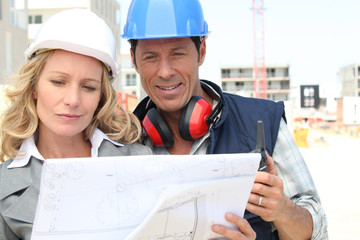 Construction worker looking at an engineer's drawing