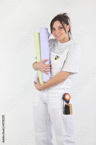 female diy holding rolls of wallpaper