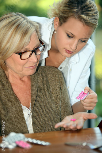 Young woman giving her grandmother medicine