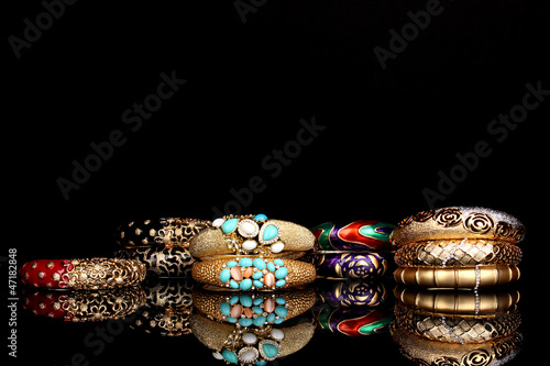 Beautiful golden bracelets isolated on black background
