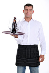 waiter holding tray with glasses and bottle