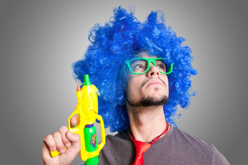 Funny guy with blue wig and water gun
