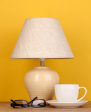 table lamp with cup and glasses on yellow background