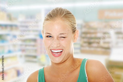 Happy young blond woman blinking.