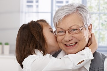 Little girl hugging and kissing granny