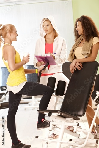 Fit girls and personal trainer at the gym