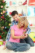 Young man makes proposal to marry girl near Christmas tree