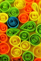 Colorful quilling on yellow background close-up