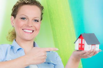 lachende frau zeigt mit dem finger auf ein neues eigenheim