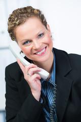 beraterin am telefon mit einem freundlichem lächeln